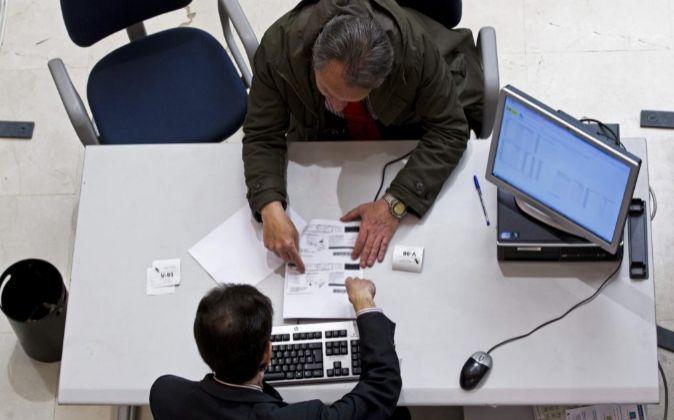 Un contribuyente presenta unos papeles ante un trabajador de la...