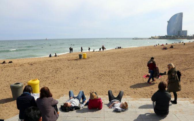 Turistas en la playa de la Barceloneta (Barcelona).
