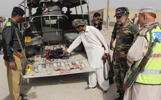 Agentes de seguridad inspeccionan el lugar de un atentado que provocó...