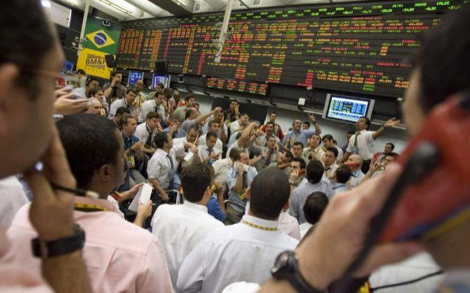 Operadores negocian  las acciones en la bolsa de valores de Sao Paulo...