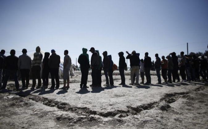 Varios refugiados hacen cola para recibir los alimentos repartidos por...