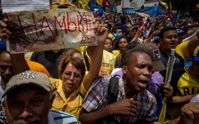 """Una manifestante sostiene un letrero con la palabra """"Hambre""""..."""