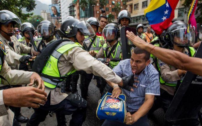 Miembros de la Policía Nacional Bolivariana (PNB) forcejean con un...