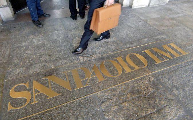 Un hombre camina cerca del logotipo del banco italiano Sanpaolo en el...