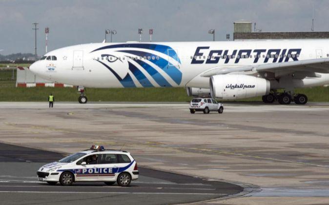 Vista de un coche de policía junto a un avión de la compañía...