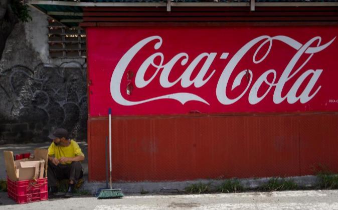 Un hombre permanece ayer junto a un kiosco de Coca-Cola en Caracas...
