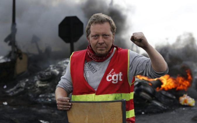 Un sindicalista ante una barricada para impedir el acceso a una...