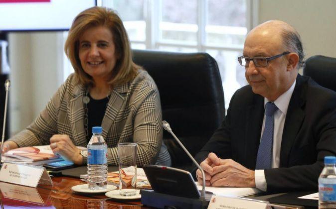 Los ministros en funciones de Empleo, Fátima Báñez (i), y de...