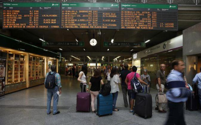 Viajeros miran los horarios en la estación madrileña de Atocha en la...