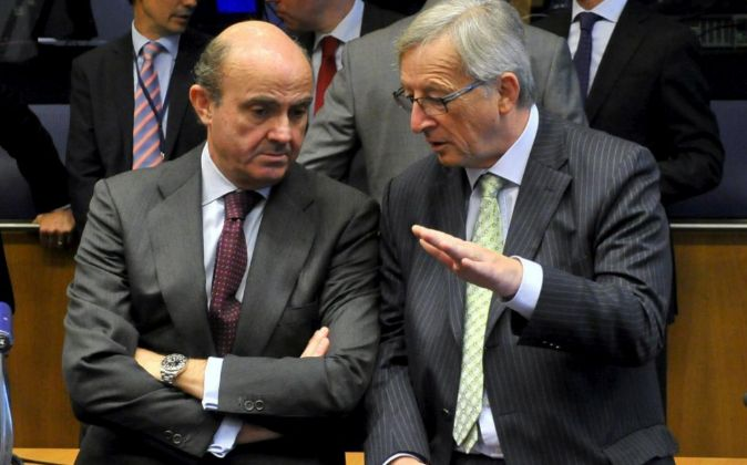 El presidente del Eurogrupo, Jean-Claude Juncker (d), conversa con el...