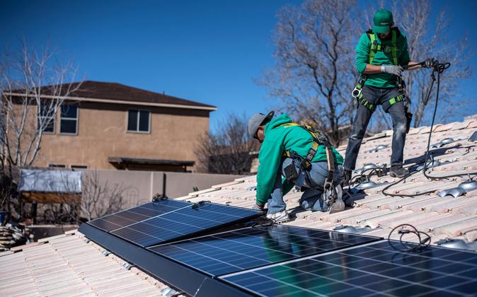 Unos trabajadores colocan varios paneles de la empresa SolarCity