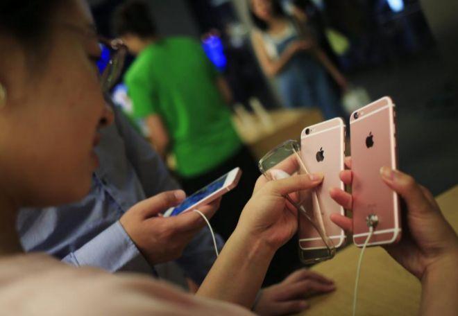 Una cliente observa un iPhone 6 en una tienda Apple en Pekín