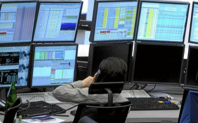 Imagen de un trader delante de las pantallas con la información...