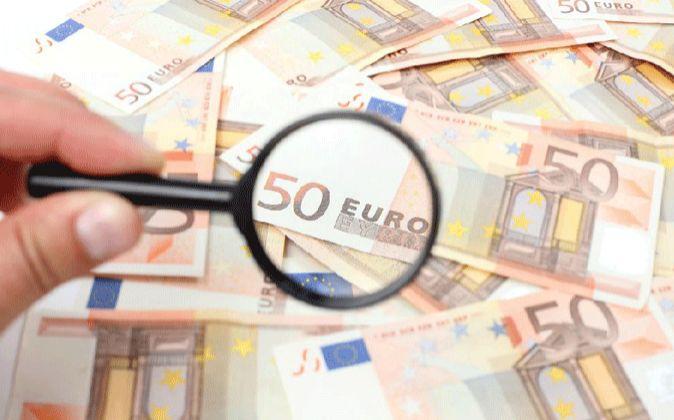 Imagen de una lupa sobre billetes de 50 euros