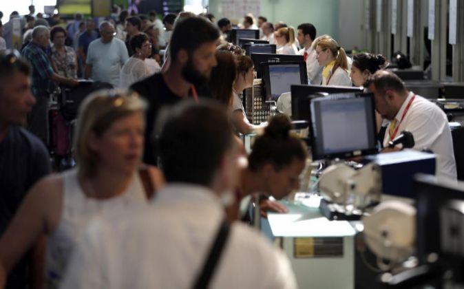 Personal de facturación de Vueling atiende a los viajeros en el...