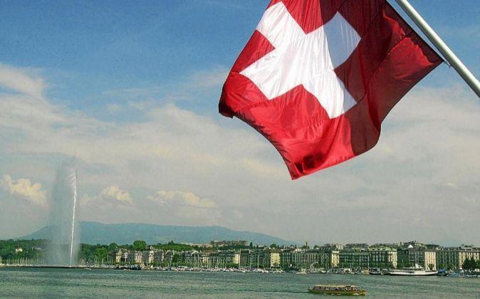 Imagen de una bandera de Suiza sobre el lago de Ginebra