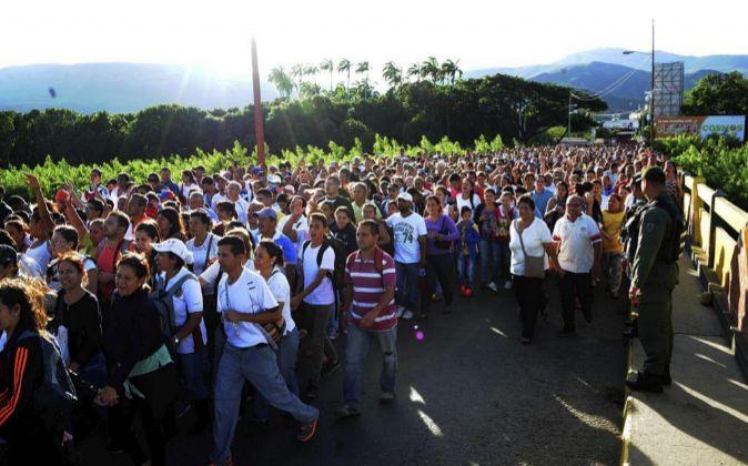 """Cientos de personas caminan por el puente fronterizo """"Simón..."""