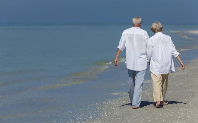 Pareja de jubilados paseando por la playa.