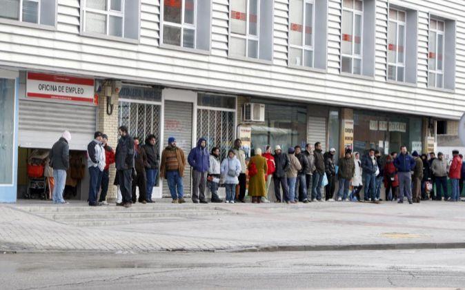Varias personas forman una larga cola ante una oficina del INEM.