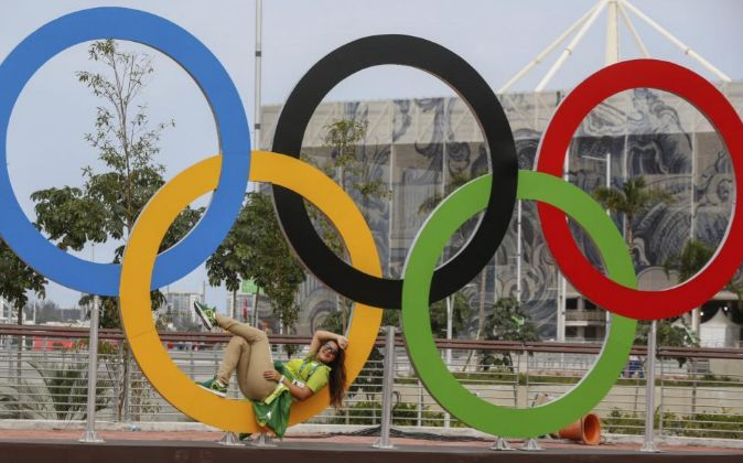 Una voluntaria descansa en los anillos olímpicos en la Villa...