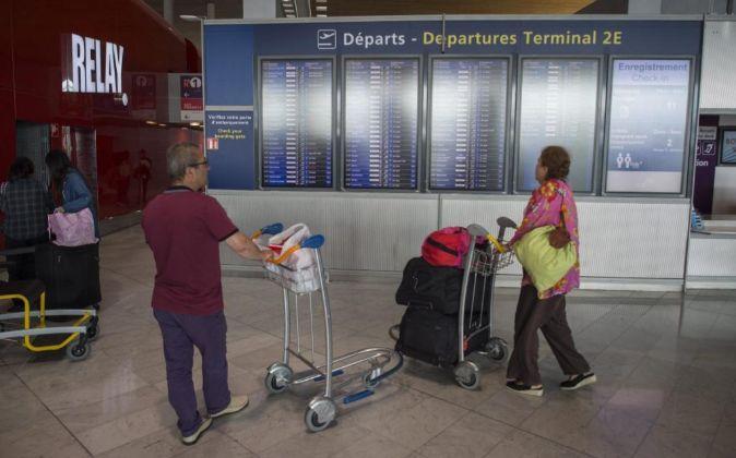 Varios pasajeros observan los paneles informativos de embarque en la...
