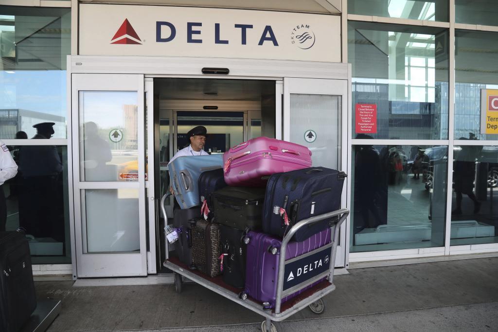 Un empleado de la aerolínea estadounidense Delta transporta equipaje...