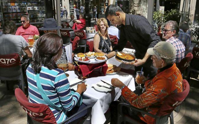 Un camarero sirve las mesas de una terraza de un bar en Barcelona.