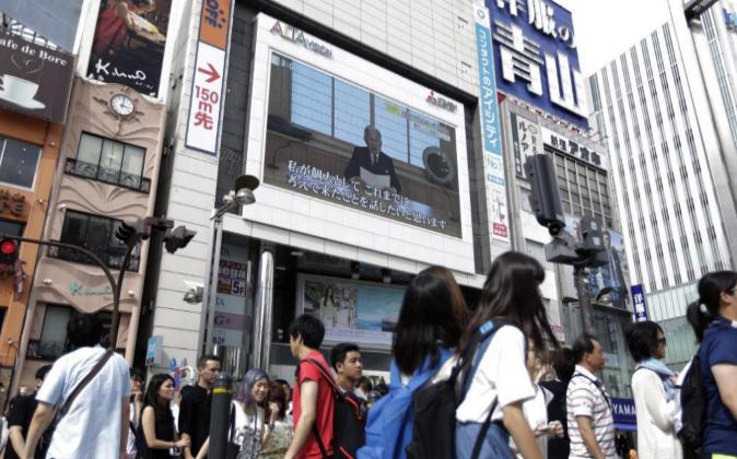 Varias personas escuchan el discurso del emperador Akihito a la...