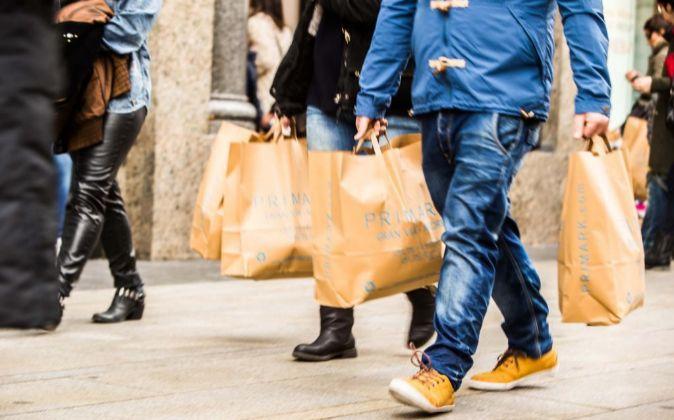 Varias personas caminando por Madrid con bolsas.