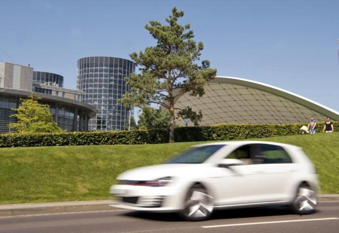 Un Volkswagen Golf pasa delante de una planta de Volkswagen en...