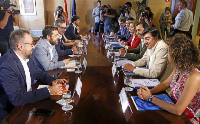 Los equipos negociadores de Ciudadanos (izqda.) y de PP (drcha.)