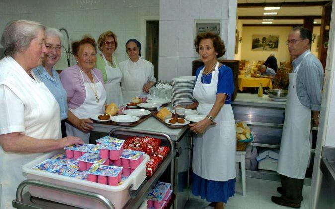 Voluntarios esperan la llegada de personas necesitadas en un comedor...