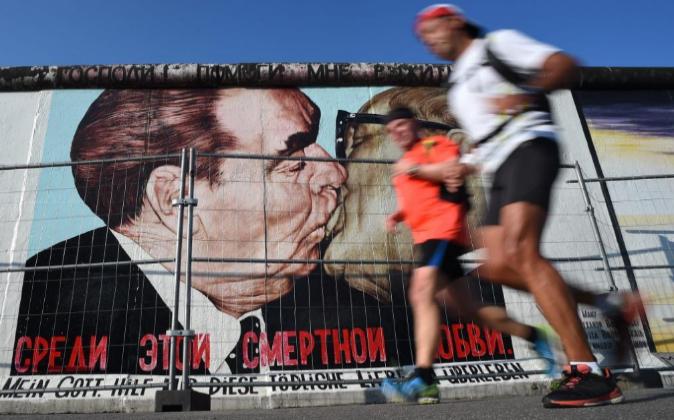 Corredores rebasan la East Gallery del muro de Berlín donde se sitúa...