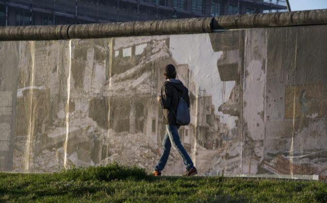 Una persona camina mientras observa las imágenes del fotógrafo...
