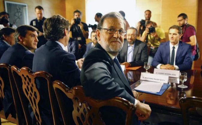 El presidente del PP y del Gobierno en funciones, Mariano Rajoy (i), y...