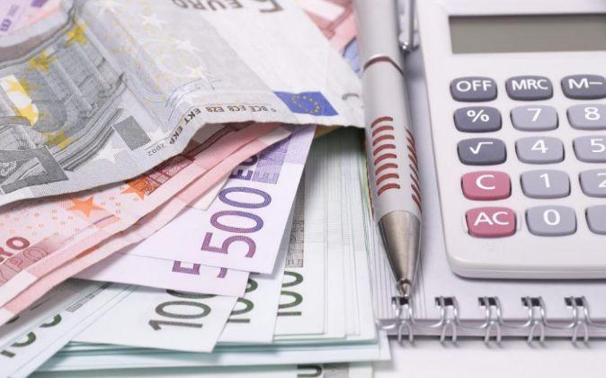 Calculadora, dinero y facturas.