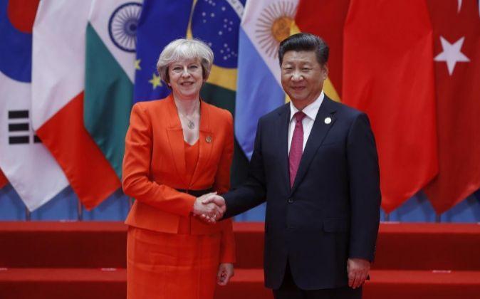 La primera ministra británica, Theresa May (i), saluda al presidente...