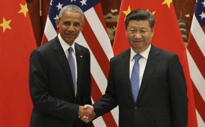 El presidente de Estados Unidos, Barack Obama (i), estrecha la mano de...