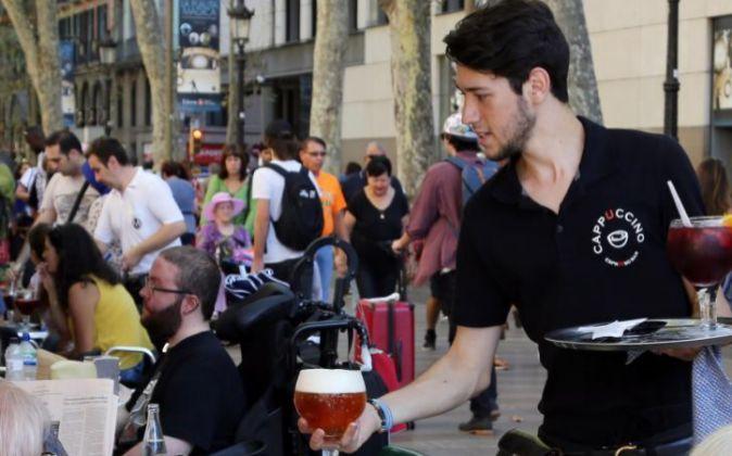 Un joven trabajando de camarero en una terraza en Barcelona.