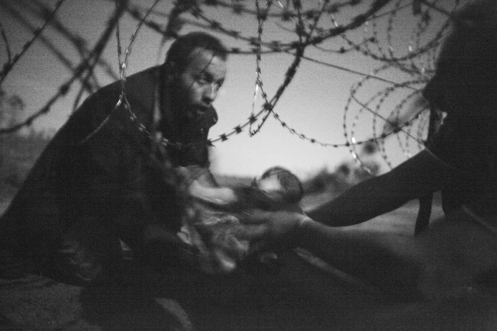Un padre entregando su bebé a través de una valla de alambre de...