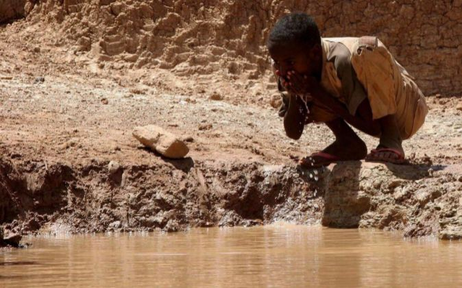 Un niño somalí bebe agua en una presa.