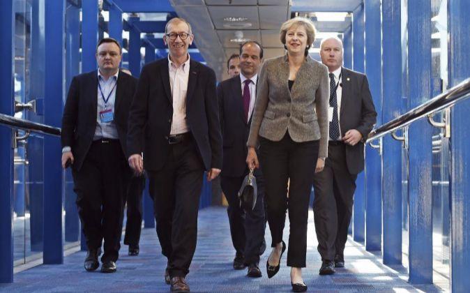 La primera ministra británica, Theresa May (2d), llega junto a su...