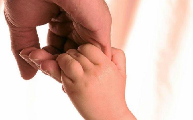 Un padre coge de la mano a su hijo.