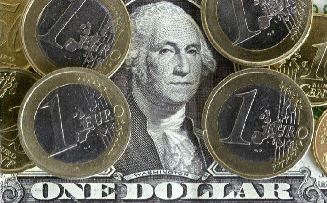 Imagen de monedas de euro sobre un billete de dólar