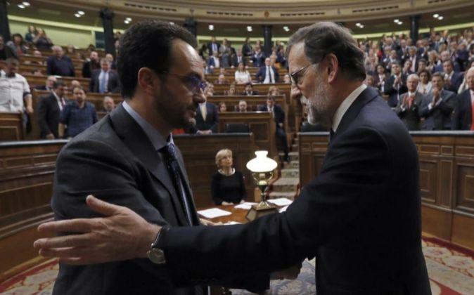 El líder del PP, Mariano Rajoy (d), es felicitado por el portavoz del...