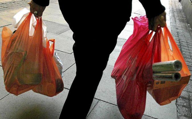 Una mujer lleva la compra en bolsas de un supermercado de Londres.