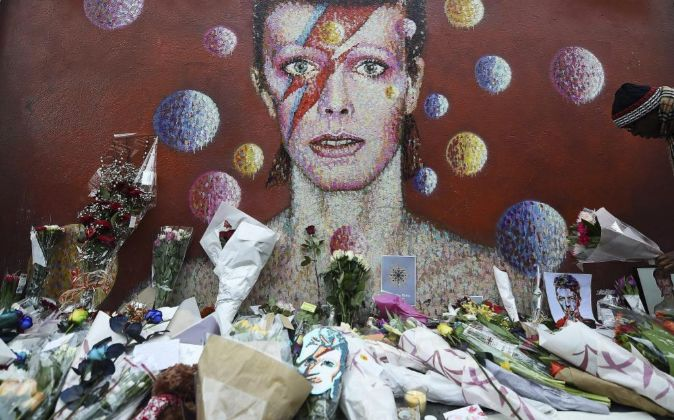 Flores y velas depositadas por los fans junto a un mural del cantante...