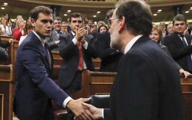 El líder del PP y presidente del Gobierno, Mariano Rajoy (d), da la...