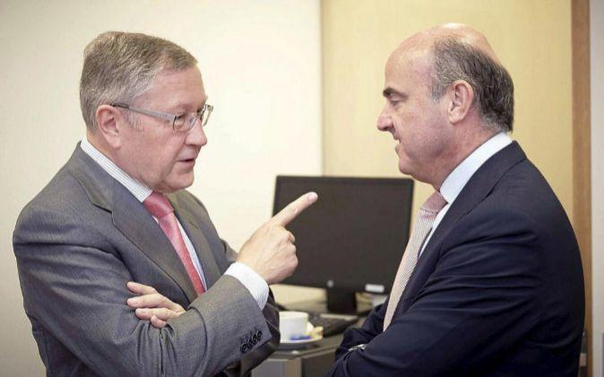 El ministro español de Economía, Luis de Guindos (d), y el director...