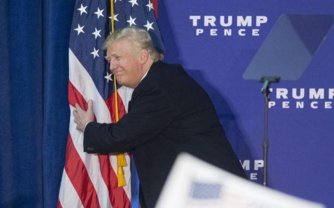 Donald Trump abrazando la bandera de los Estados Unidos.